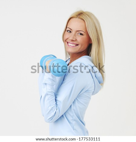 Sport woman in blue sportswear with dumbbells - stock photo