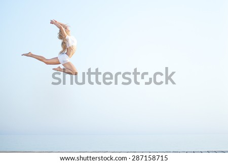 Sport woman jumping against beautiful sea. Freedom, enjoyment concept. - stock photo