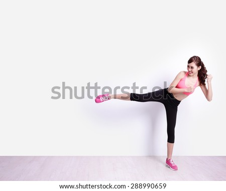 Sport Woman kick something with white wall background, great for your design or text, asian beauty - stock photo