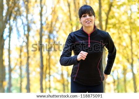 Sport woman running exercise outdoors in park. Cheerful hispanic caucasian female athlete working out. - stock photo