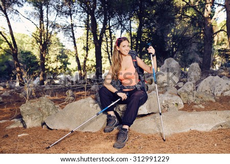 Sport Woman sitting on a rock with a backpack and sunglasses and hiking shoes - stock photo