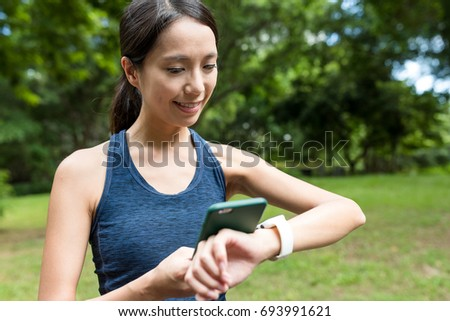 Sport woman using smart watch connect to mobile phone in the park