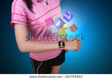 Sport woman wearing touchscreen smartwatch with colorful app icons isolated on blue background - stock photo