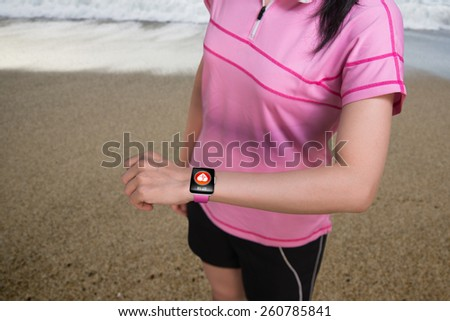 Sport woman wearing touchscreen smartwatch with health sensor app icon on natural sea beach background - stock photo