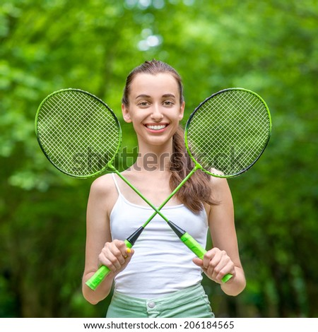 Sport woman with badminton rackets in the park - stock photo