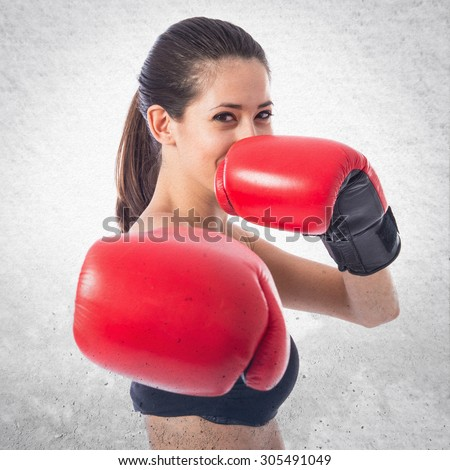 Sport woman with boxing gloves over textured background