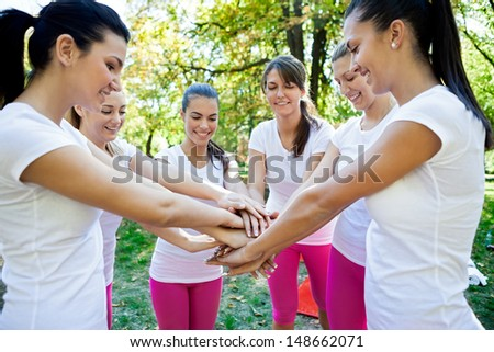 Sport women team with arms together in cooperation - stock photo