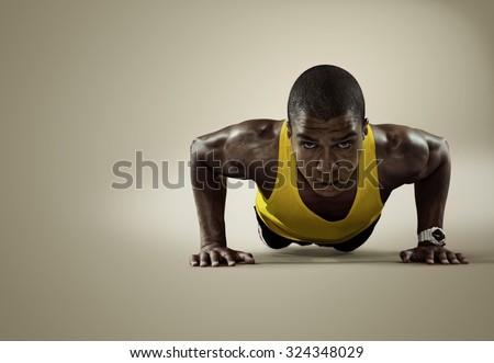 Sport. Young athletic man doing push-ups. Muscular and strong guy exercising. Isolated  - stock photo
