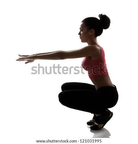 sport young woman athlete doing squatting exercise, active fitness girl silhouette studio shot over white background - stock photo