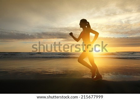 Sport young woman running on the beach at sunrise, asian - stock photo