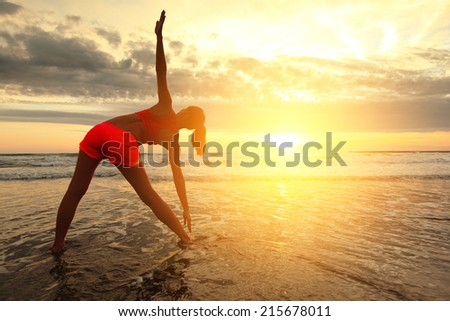 Sport Young woman silhouette practicing yoga on the sea beach at sunset - stock photo
