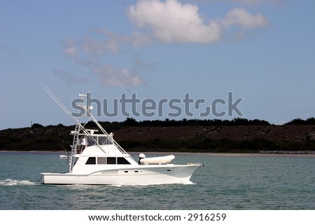sportfisherman boat on crystal clear blue tropical waters - stock photo