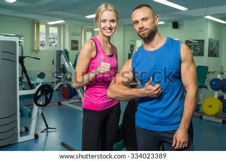 Sporting a young couple in the gym. Healthy Lifestyle. Women's and Men's Fitness. Work on your body. Photos for sporting magazines, posters and websites. - stock photo