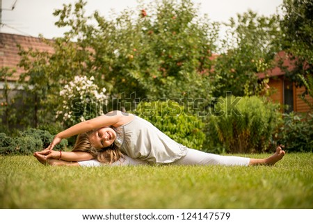 Sporting on grass - smiling little child exercising outdoor in backyard - stock photo