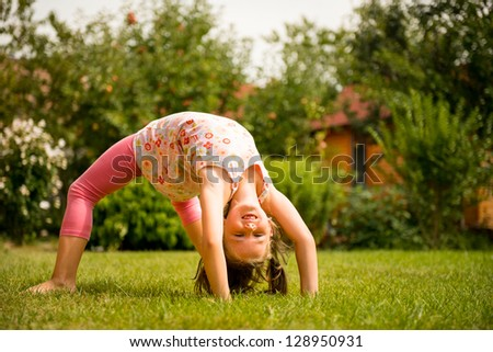 Sporting on grass - smiling little child making bridge outdoor in backyard - stock photo