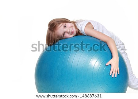 Sporting young girl jumping on a fitball and smiling on a white background - stock photo