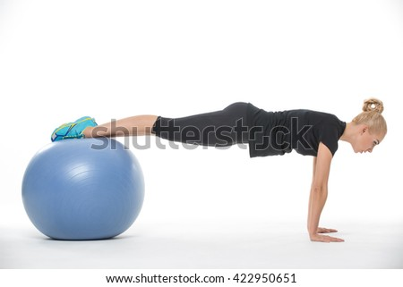 Sportive blonde girl in the sportswear with a blue fitball on the white background in the studio. She wears cyan-yellow sneakers, black pants and black t-shirt. She leans on her hands while her feet
