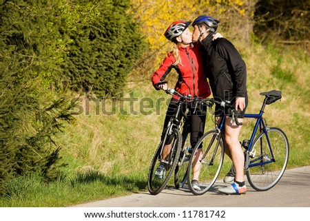 Sportive couple on bicycles kissing: it's spring, you know...