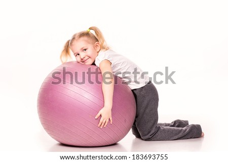 Sportive cute little girl on a fit ball isolated over white - stock photo