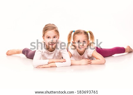 Sportive cute little girls lying on a floor isolated over white - stock photo
