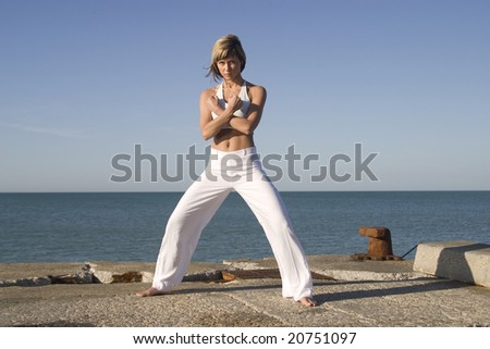 Sportive girl in yoga position next to the sea - stock photo