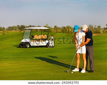 Sportive happy family playing golf on a golf course - stock photo