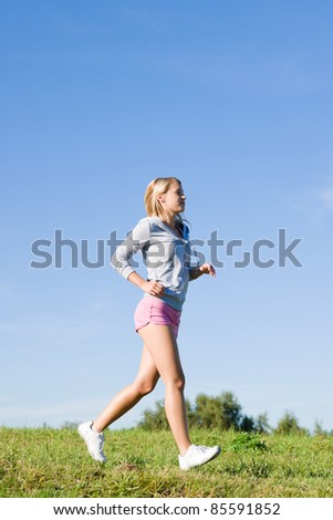 Sportive jogging young happy woman meadows blue summer sky