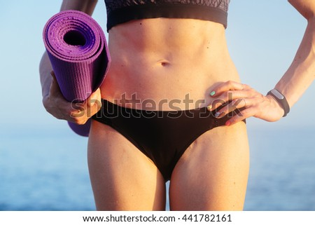 Sportive leisure woman with perfect body holding yoga mat. Health life concept. Copy space text Toned image.