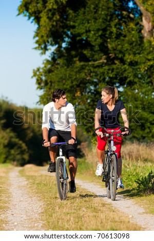 Sportive Man and woman exercising with bicycles outdoors, they are a couple