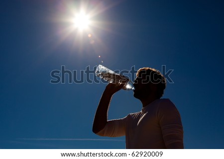 Sportive man drinking water from a bottle against a blue sky background under a hot sun - stock photo