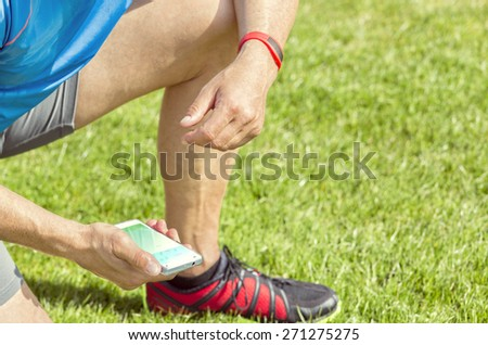 Sportive man kneels on a lawn and checks his fitness results on a smartphone. He wears a fitness tracker wristband on his left arm. - stock photo