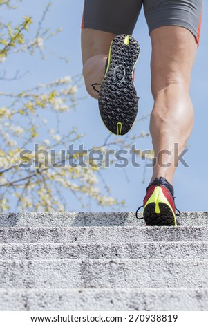 Sportive man runs up the stairs. In the background can be seen the blossoms on the branches  of a cherry tree on blue sky background. It symbolizes  spring outdoor activities after a long winter. - stock photo