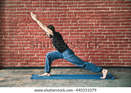 Sportive man with a beard wearing black T-shirt and blue trousers doing yoga warrior position on blue matt at wall background, copy space, portrait, virabhadrasana. - stock photo