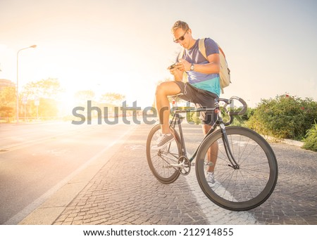 Sportive man with bicycle at sunset  - stock photo