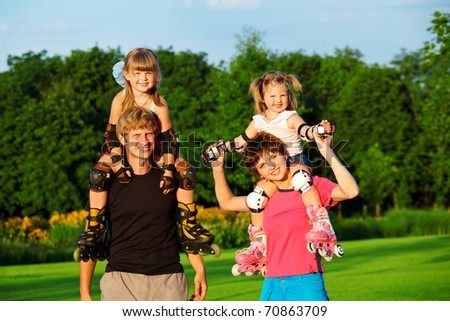 Sportive parents with kids in roller skates - stock photo