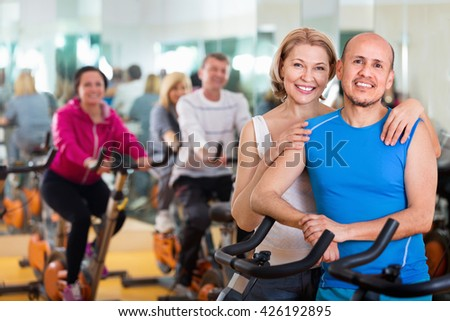 Sportive pleasant smiling couple in a fitness club with friends - stock photo