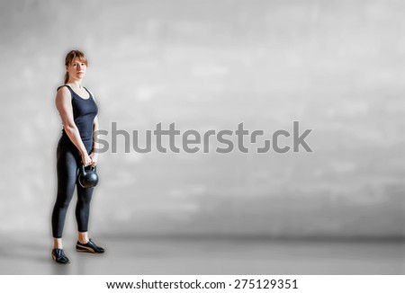 Sportive redheaded woman doing exercises with kettlebell