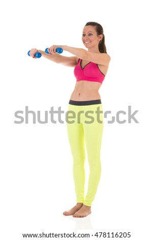 Sportive smiling brunette woman in sports neon yellow leggings and pink bra doing complex exercises for muscles of hands using blue dumbbells on white background