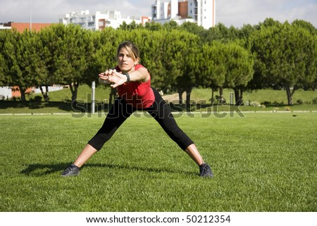 Sportive woman doing exercise on an urban park - stock photo