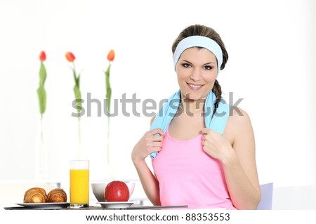 sportive woman is having a tasted french breakfast - stock photo