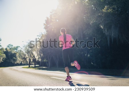 Sportive woman running outside at sunrise on the road. Fitness and wellness concept. - stock photo