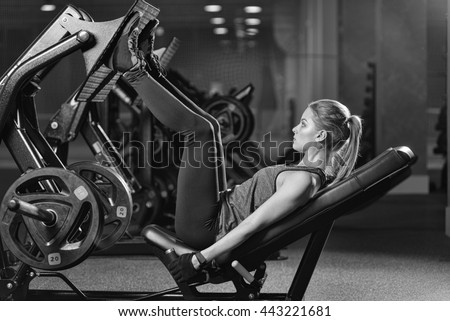 Sportive woman using weights press machine for legs at the gym. Pretty brunette exercising in a simulator. Working her quads at machine. Black and white. - stock photo