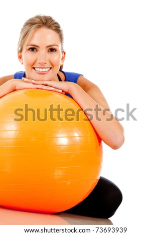 Sportive woman with a pilates ball - isolated over white