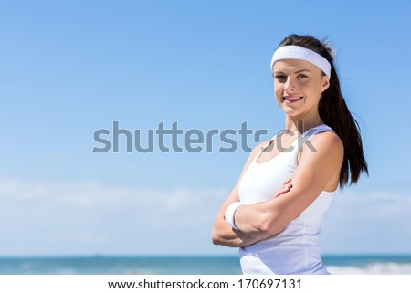 sportive young fitness woman with arms crossed on beach