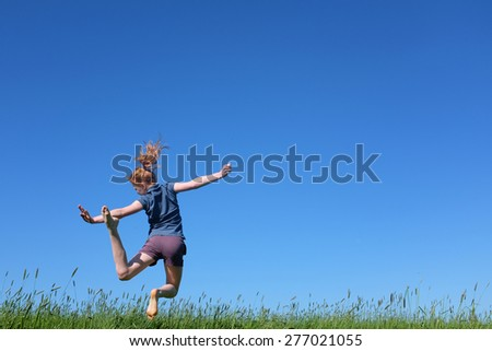 Sportive young girl jumping in meadow with blue sky - stock photo