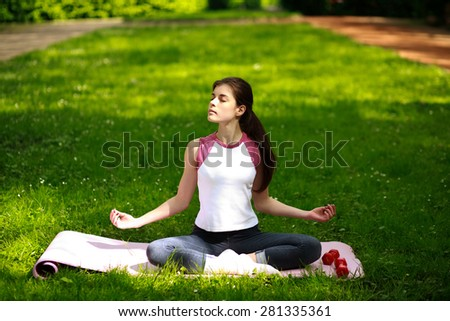 Sportive young woman relaxing in sunshine, doing yoga exercises, in green park - stock photo