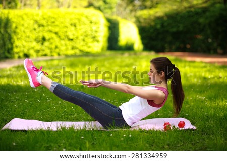 Sportive young woman stretching, doing fitness exercises in green park, workout outdoors - stock photo