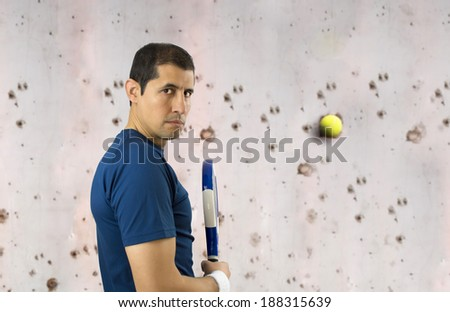 sportman vents his anger with a wall with a ball and paddle racket - stock photo