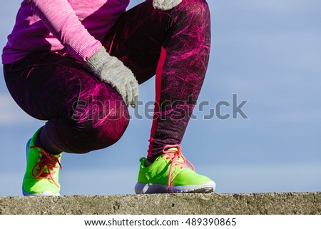 Sports and activities. Part body of training active sporty girl outside. Slim fit legs in vivid color yellow shoes against sky.