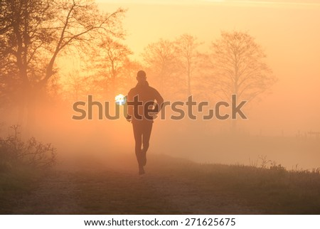 Sports and healthy lifestyle concept: silhouette of a man running during a foggy sunrise in the countryside, with the sun in the background. - stock photo